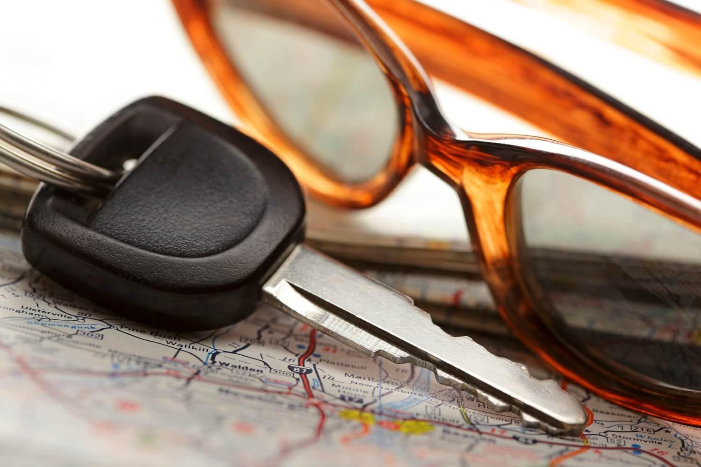Autoschlüssel, Sonnenbrille und Landkarte werden auf der Reise benötigt
