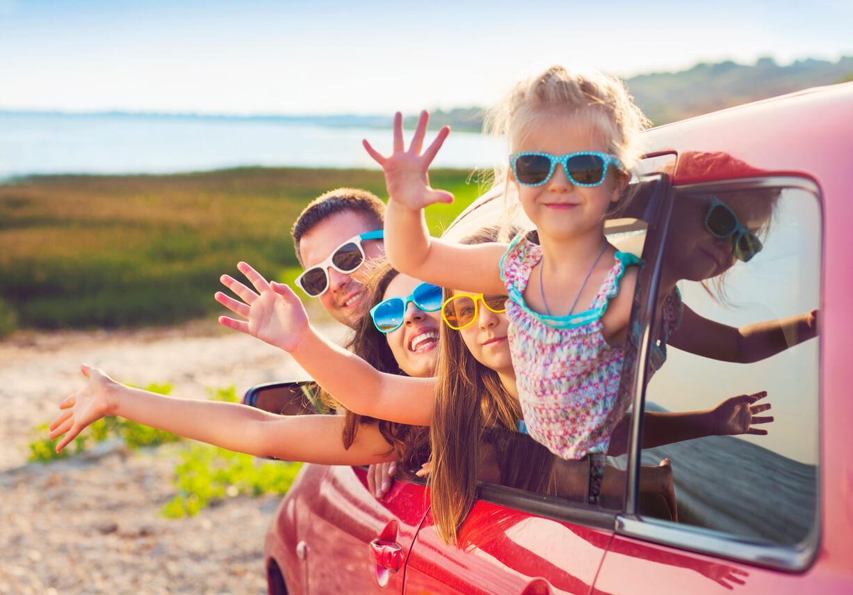 Familie mit Kindern im Auto am Strand