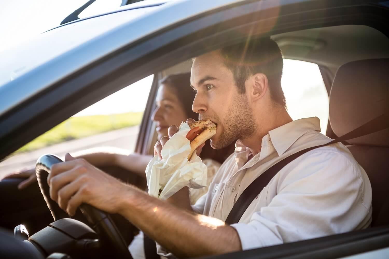 Ein Paar fährt in den Urlaub und isst ein Butterbrot im Auto. Das Autofenster ist offen. Der Mann fährt, die Frau schaut auf die Straße.
