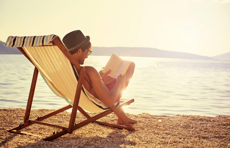 Mann liest am Strand