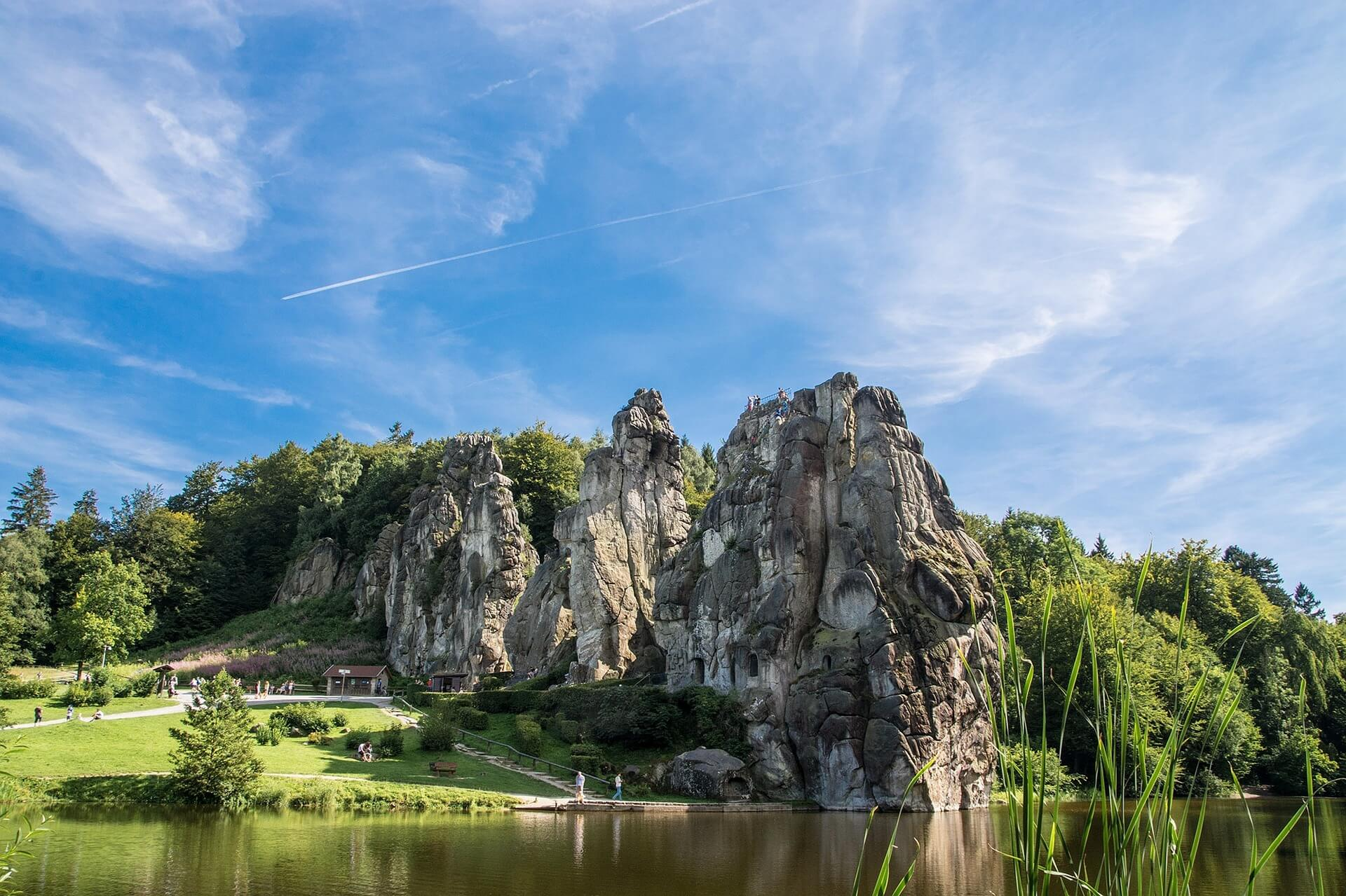 Der Anblick der Externsteine am Ende des Waldwegs ist beeindruckend: Die Felsformation ragt bis zu 40 Meter in die Höhe, zwei der riesigen Steine sind durch eine filigrane Brücke aus dem 19. Jahrhundert verbunden. Davor erstreckt sich ein See, hinter den Steinen wieder der Wald. Zu sehen gibt es ein Trogbogengrab sowie ein Relief, das im Mittelalter in einen der Felsen gehauen wurde.