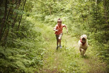 Young boy running with dog in woods