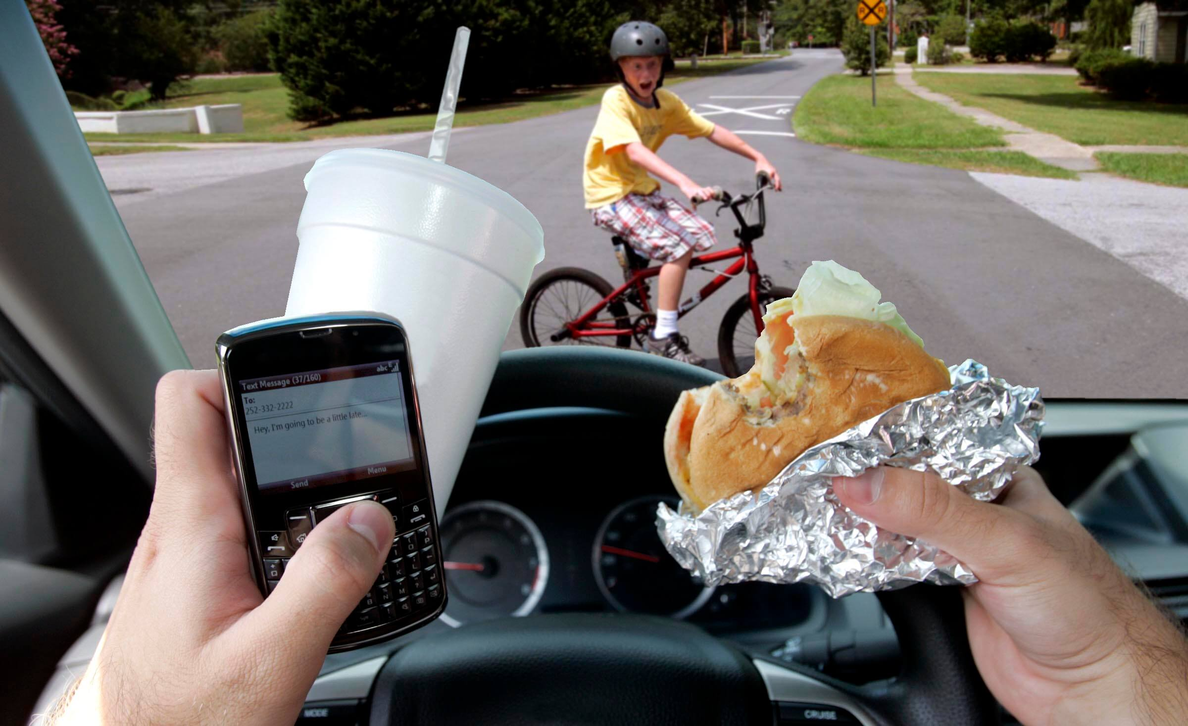 Driver holding burger, soda and phone while driving near a child riding bike