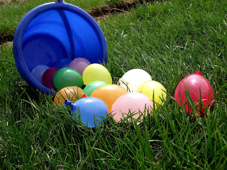 Picture of water balloons on the grass. No. 35 Start a waterballoon fight from the 100 things to do before your 12 list.