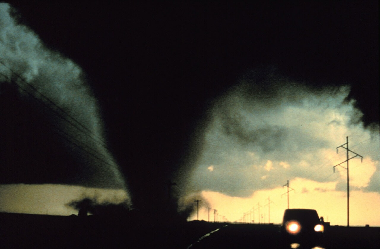 Dark threatening tornado with a car driving away from it