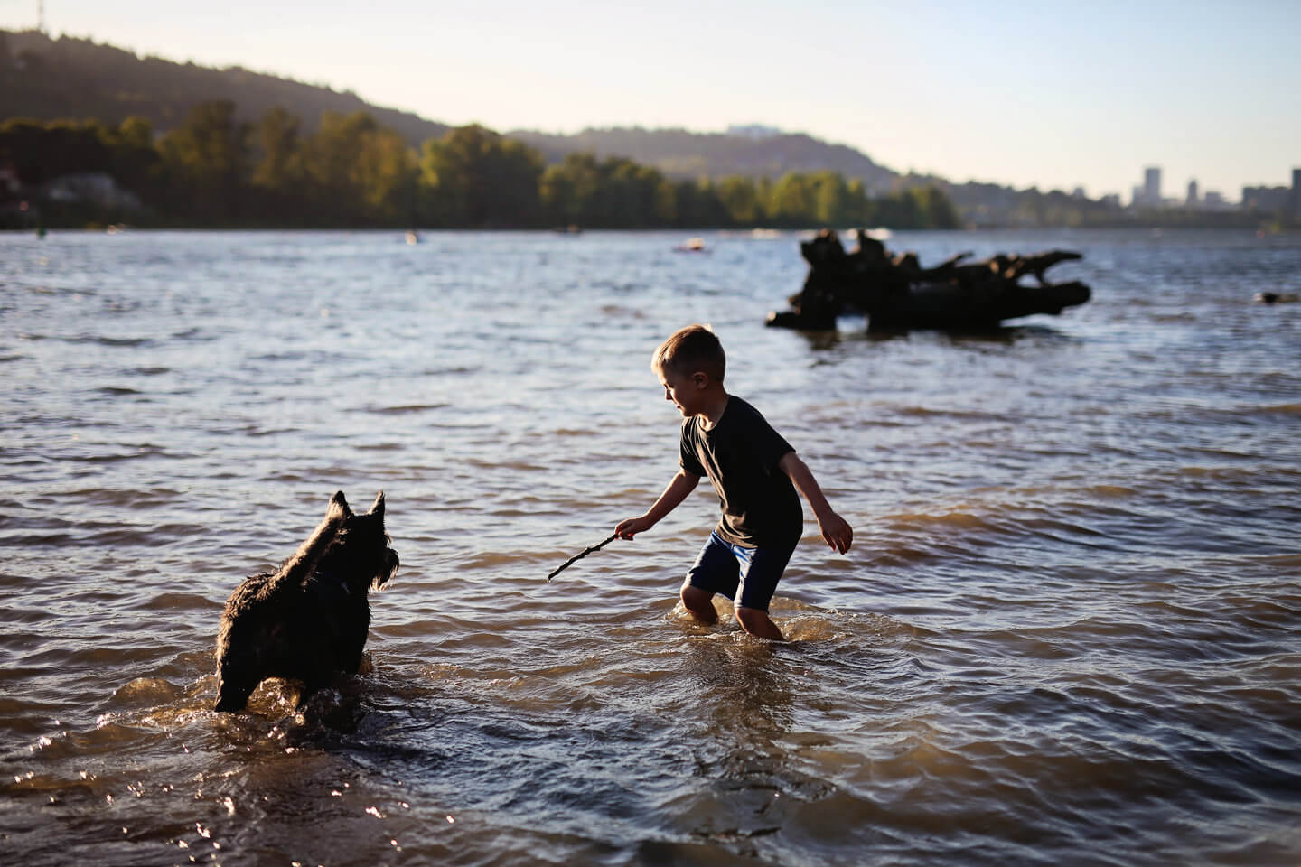 Boy and his dog enjoying time at the Willamette River in Portland, Oregon