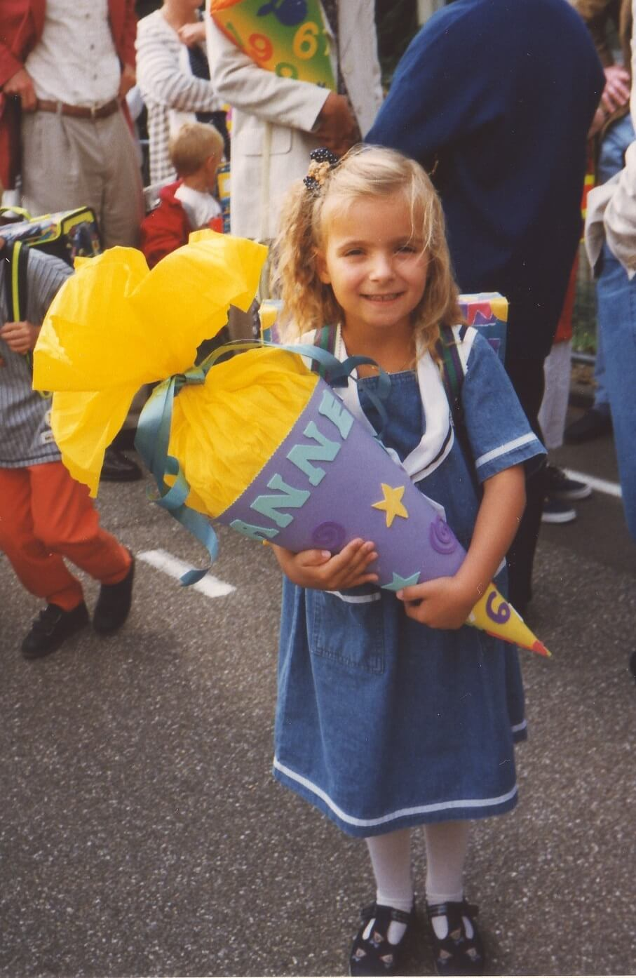 A young girl with blonde hair holds a Schultüte (paper cone) in front of a crowd of people.