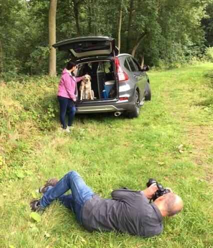 photographer lying in the grasss taking photo of woman standing next to SUV with dog in the trunk