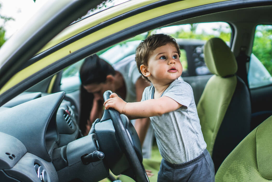 A child standing on a driver's seat pretending to drive a car.