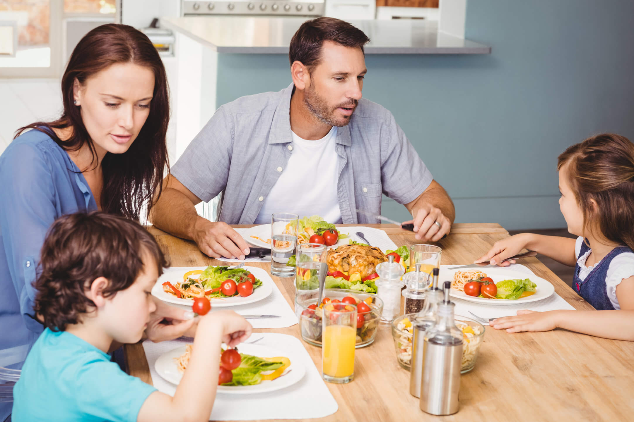 Family having meal together while sitting at dining table in home
