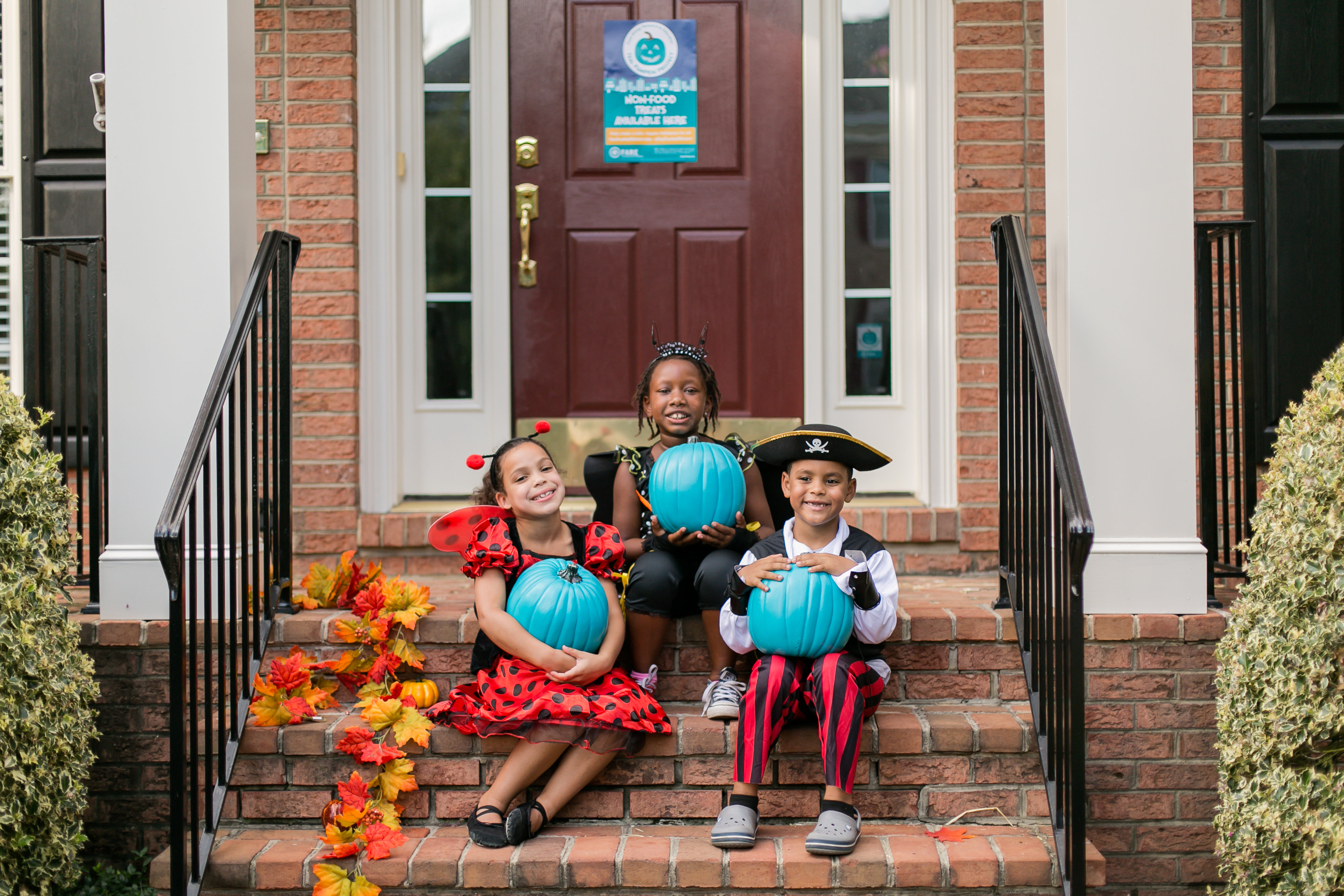 Three kids in Halloween costumes sit on the brick stoop of their home, all holding teal pumpkins on their lap.