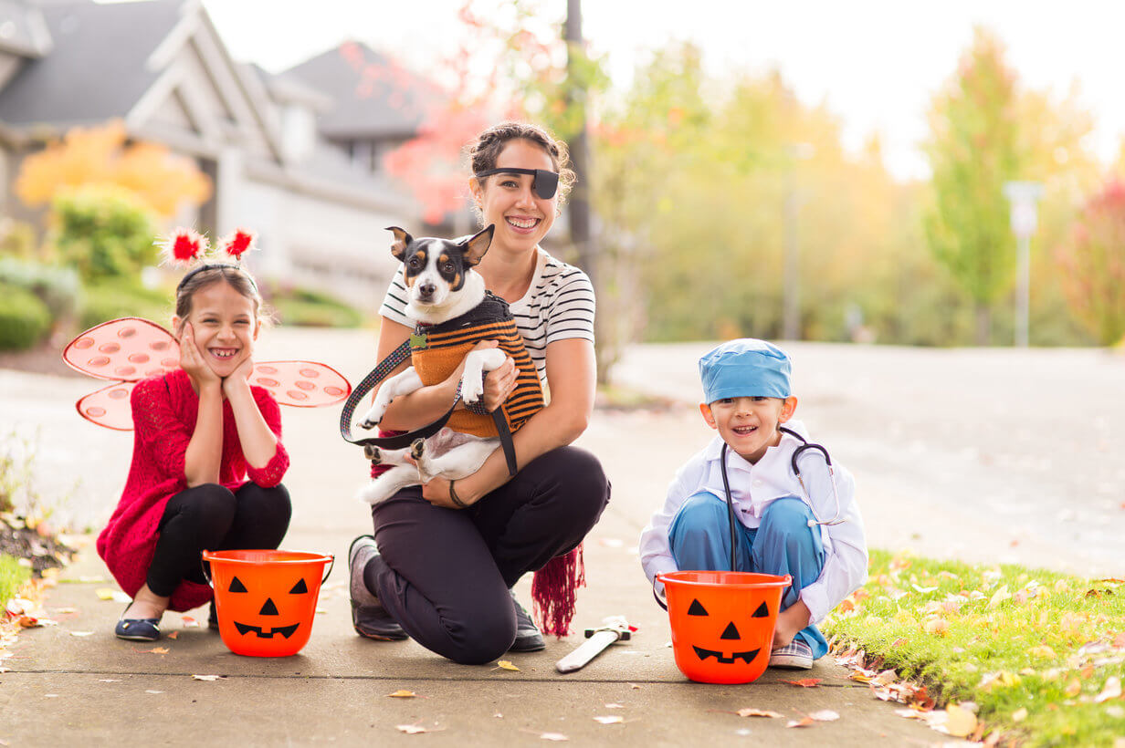 Two children dressed up for Halloween as a ladybug and a doctor go trick or treating with their mom who is dressed as a pirate and their dog