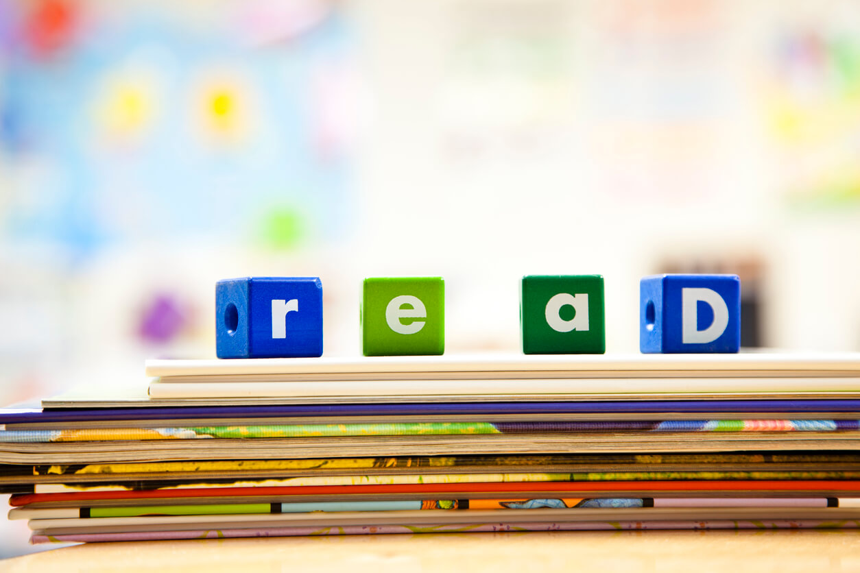 A stack of picture books has letter blocks on top that spell out read.