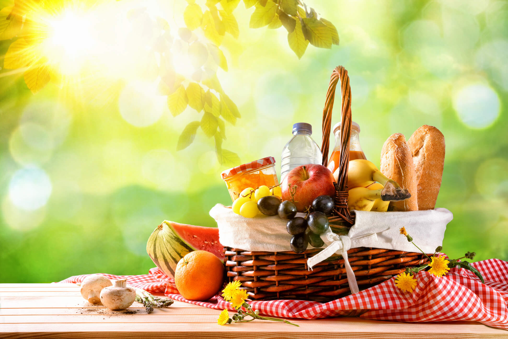 Picnic wicker basket with food on table in the field with green nature background.