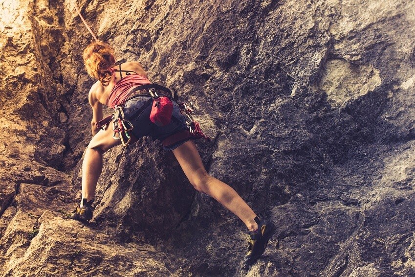 Athletic young woman is rock climbing at sunset