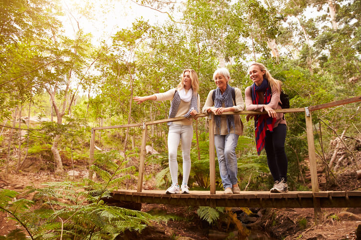 Grandmother, mother and daughter on a bridge in a forest